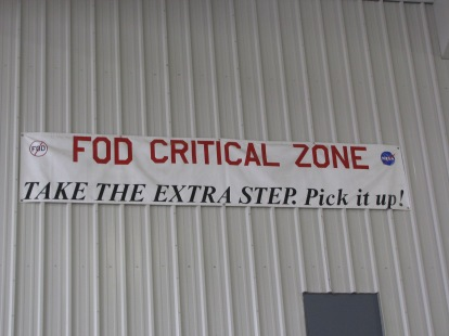 "FOD sign in the hangar. FOD means ""foreign object debris"" or ""foreign object damage."" Even a small screw on the ground can get sucked into an engine and cause damage."